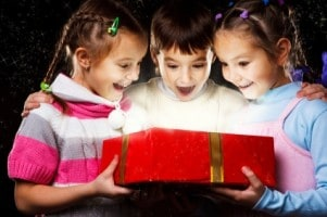 Three excited kids look happily into Christmas gift